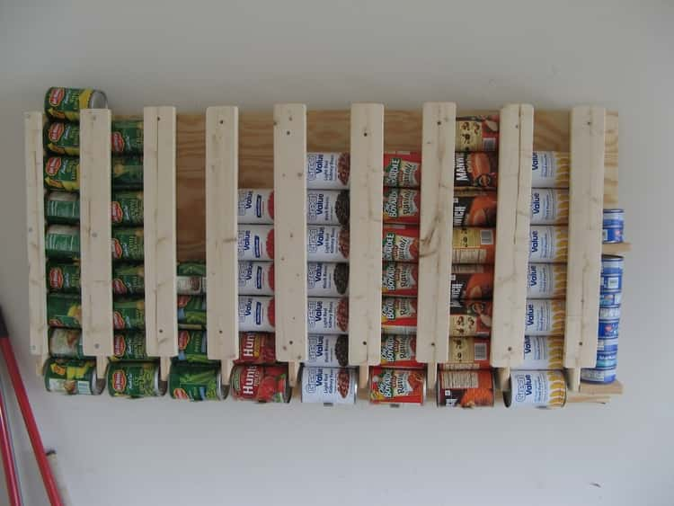 DIY wall mounted canned food organizer with canned goods stacked inside