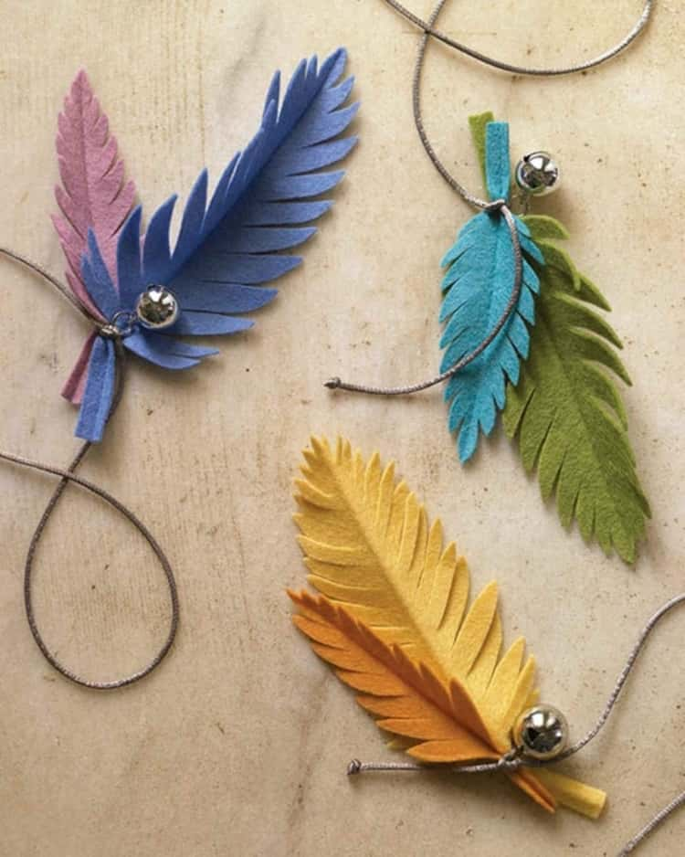 3 cat toys made from felt fabric shaped to look like a feather and a bell