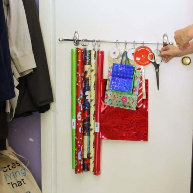 hanging wrapping paper, bags, ribbons, and scissors on a rod and hooks and rings on back of door of closet