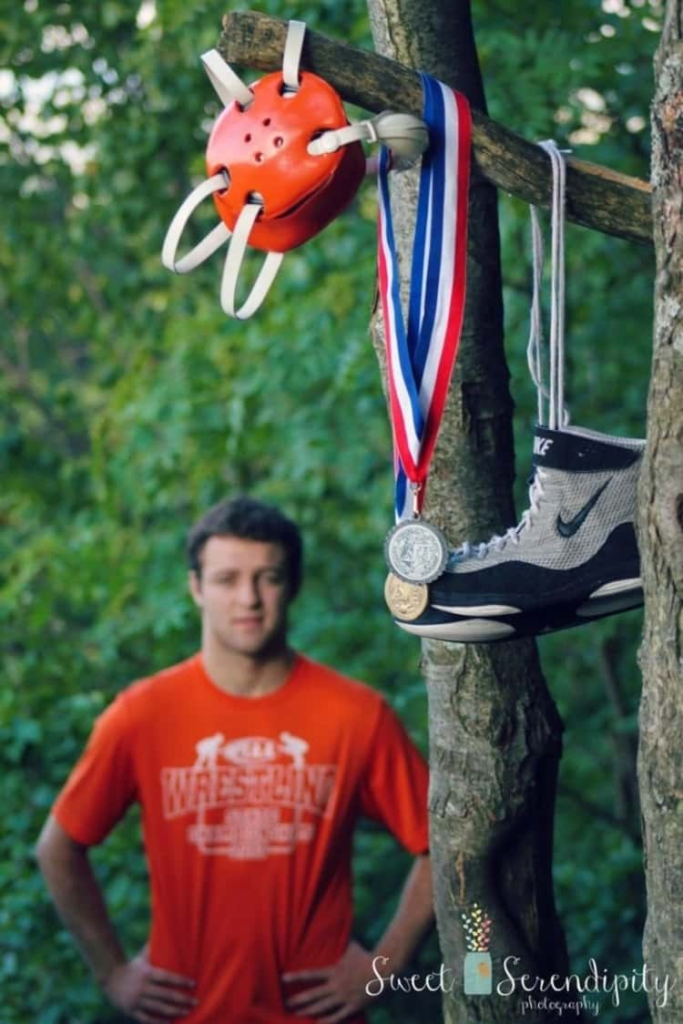 a wrestler's medals, helmet, and shoe hanging on a tree and a guy seen out of focus in the image