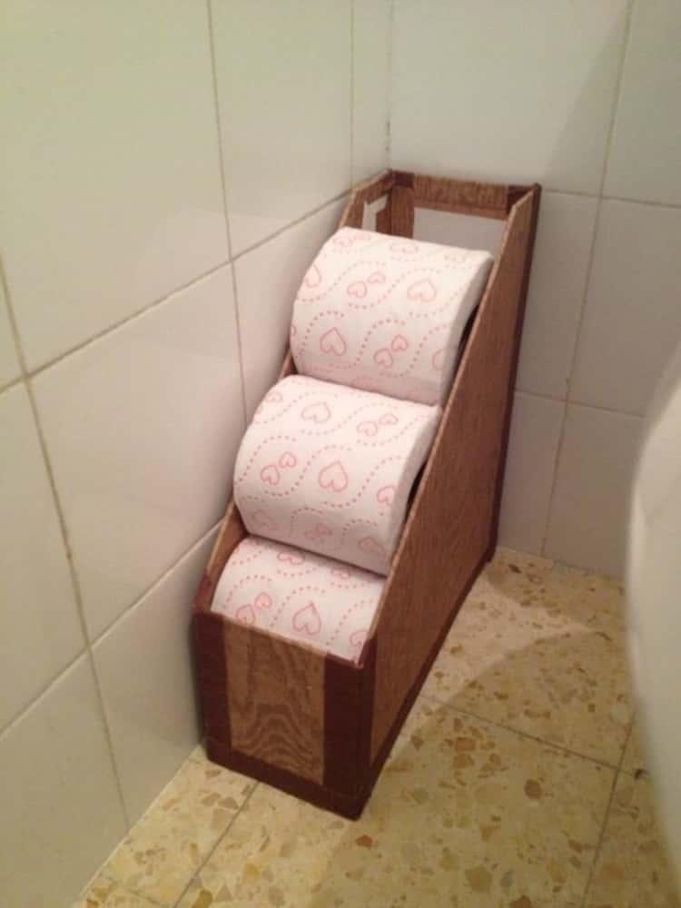 magazine holder repurposed to store toilet paper rolls in bathroom