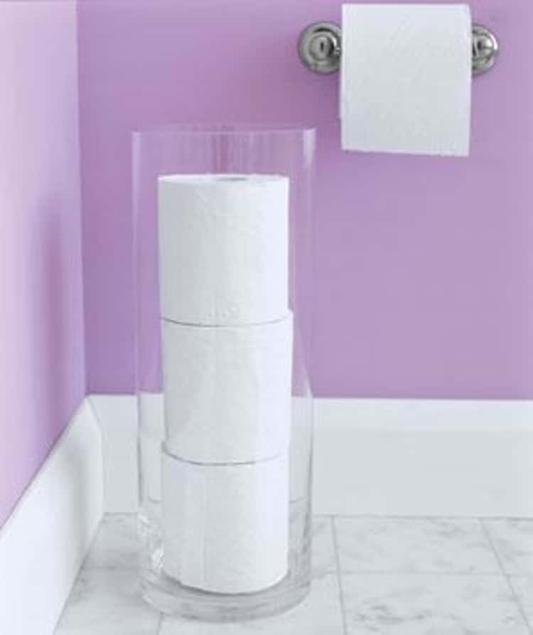 toilet paper storage in bathroom using a tall hurricane vase for elegant and clean look
