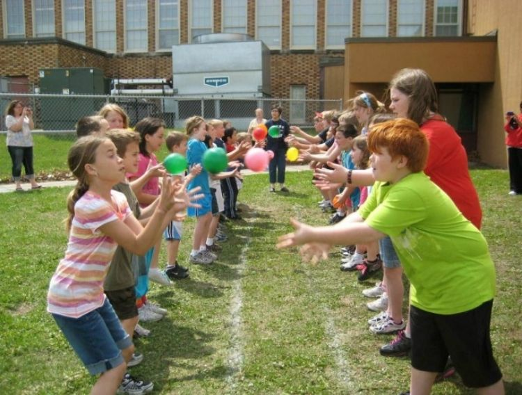 a group of kids playing pass the water balloon