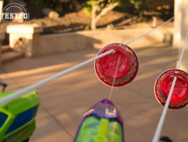 watergun shooting at red paper plates tied to a string