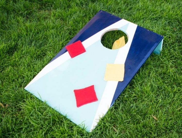bean bag in hole game with red and yellow bean bags