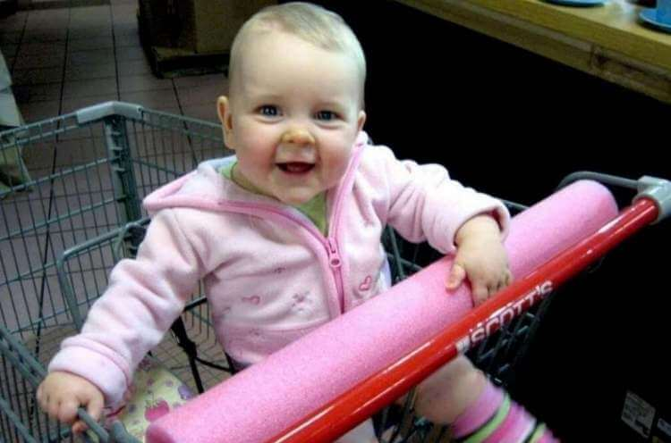 baby in shopping cart with handle covered with a pool noodle
