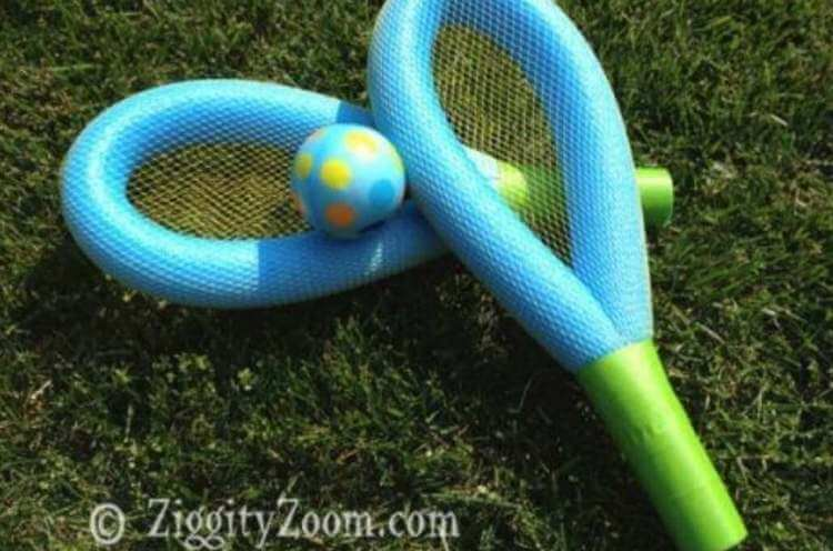 DIY uses for pool noodles- a racket and ball set made from pool noodles, netting, and tape resting on the grass