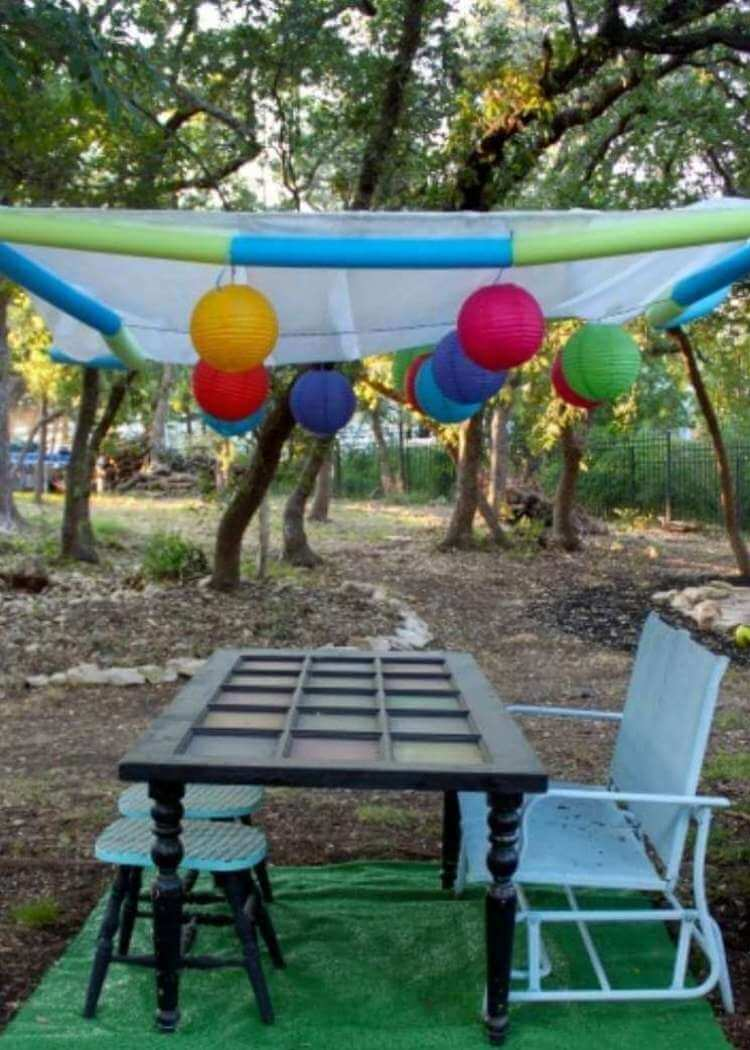 uses for pool noodles- a backward overhead canopy made of white netting and colorful pool noodles string together and suspended in the air