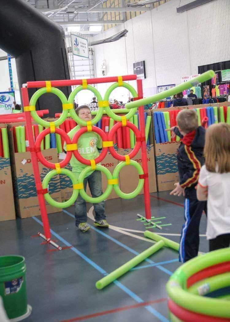 uses for pool noodles- kids playing toss with a tic tac toes style target made of pvc pipe and covered in pool noodles