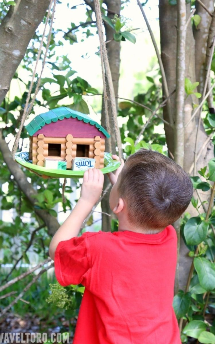 boy hanging up his Lincoln Log birdhouse