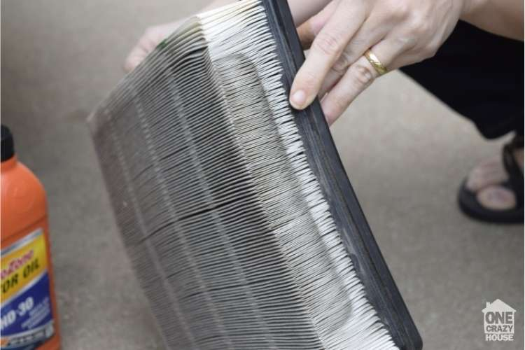 OneCrazyHouse Easy Car Repairs hand holding a car AC filter