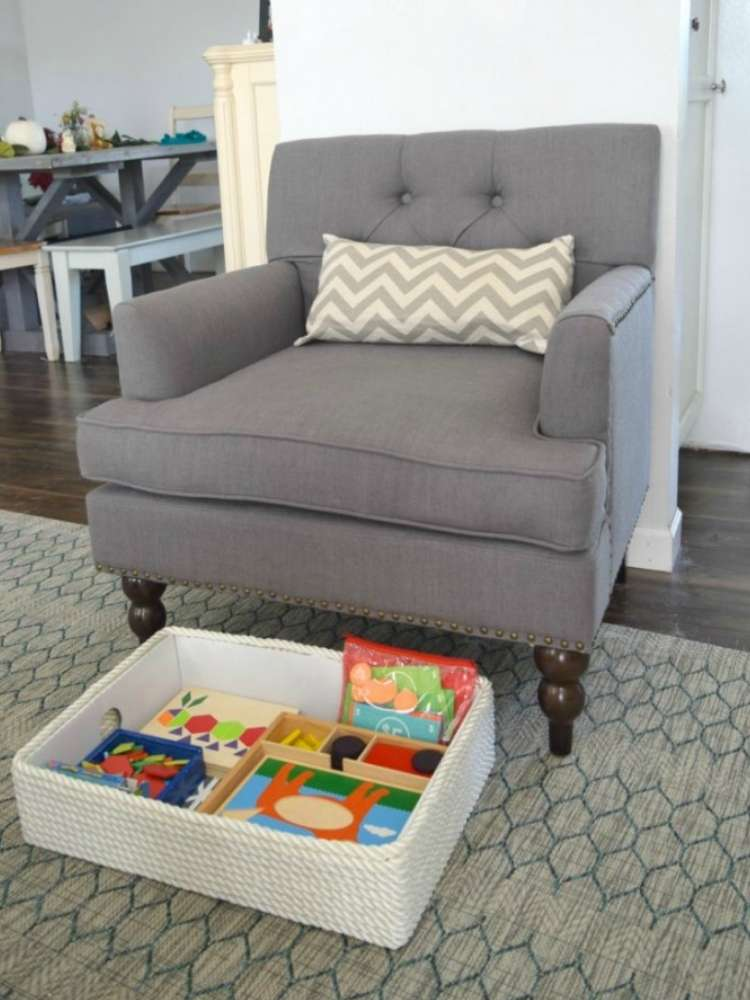 OneCrazyHouse kid friendly living room ideas Bin with toys pulled out from under chair where it's being stored in living room