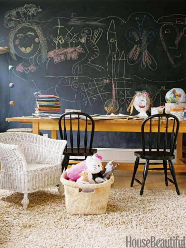 OneCrazyHouse kid friendly living room ideas wall covered in chalboard paint with chalk drawings with a table in front of wall, arm chair off to the side