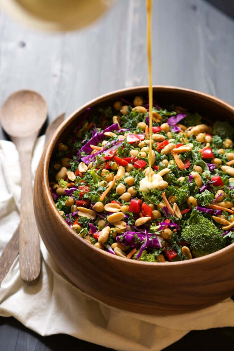 Rainbow kale salad with a fresh peanut Dijon dressing being drizzled on