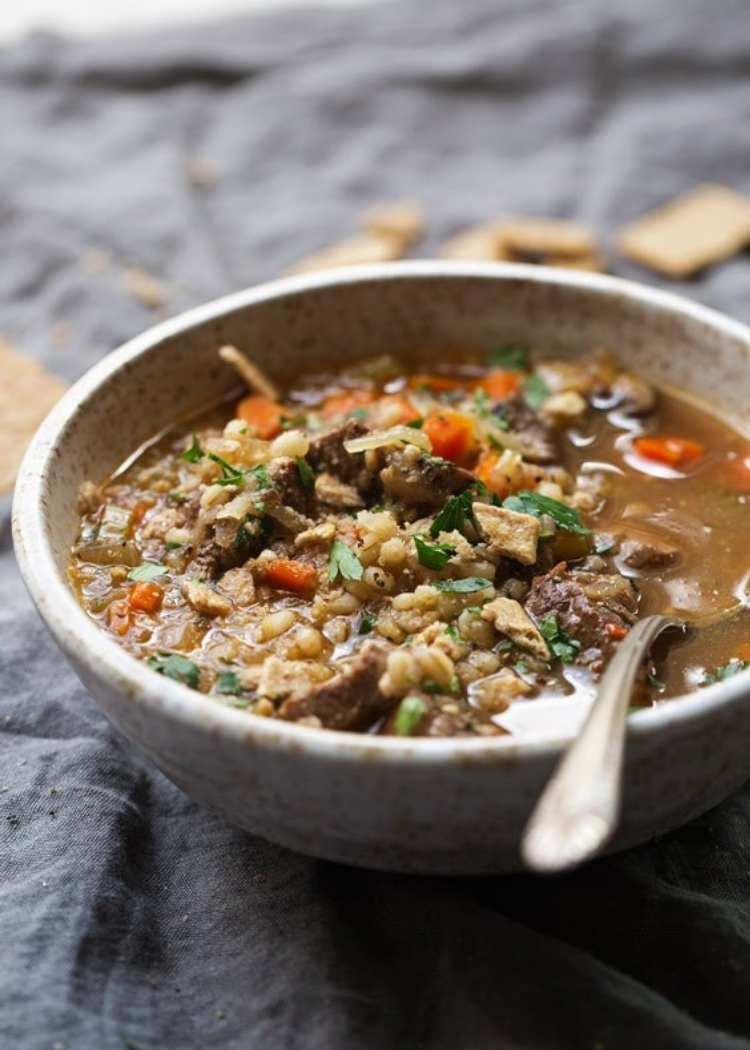 Instant Pot soup recipe for Beef and barley soup - warm hearty bowl of soup with tender chunks of beef, veggies, and tender barley with a spoon ready to eat.