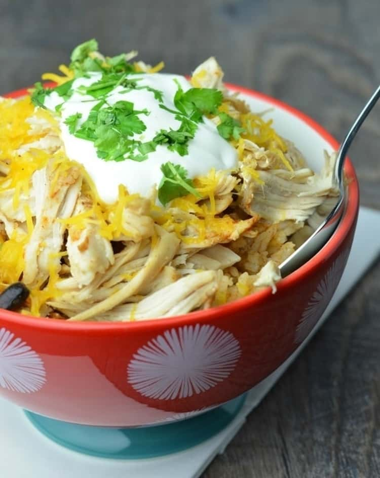 chicken taco bowl ingredients in a bowl topped with sour cream and cilantro