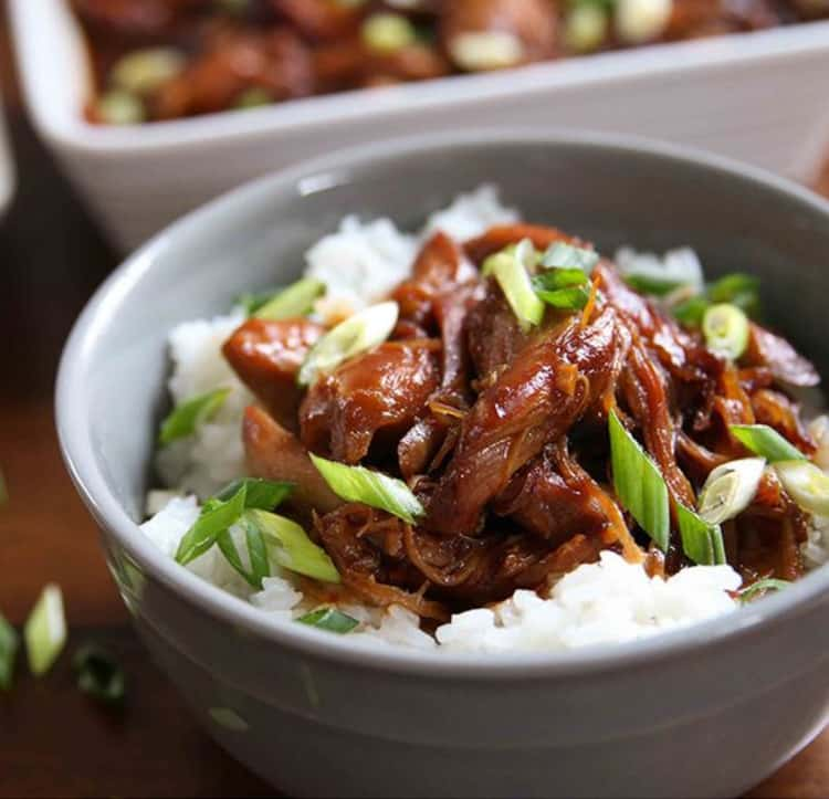 bowl of honey bourbon chicken over white sticky rice with and topped with diagonally sliced green onions or sifflets