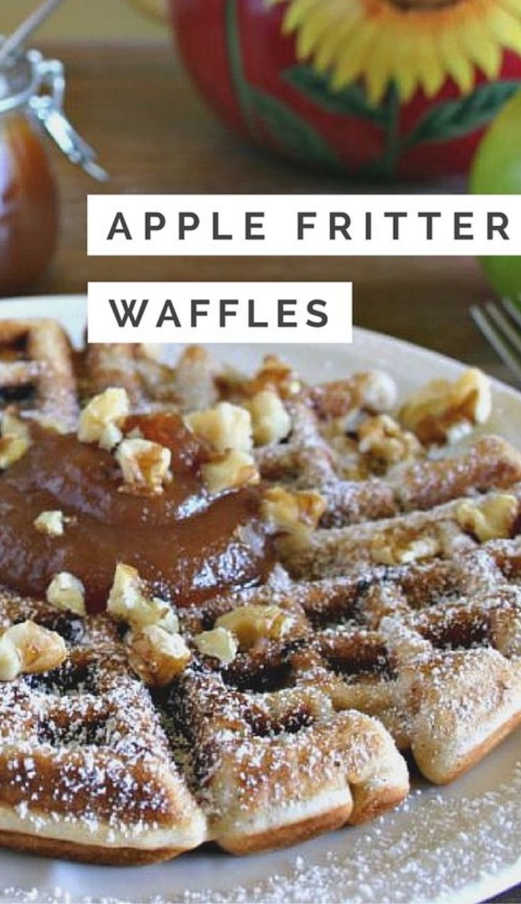 a plate full of apple fritter waffles topped with a dollop of apple butter and sprinkled with powdered sugar and toasted nuts