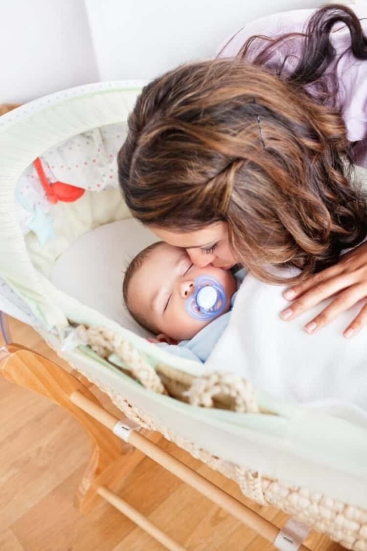 a mom kissing a baby who's asleep and has a pacifier in their mouth