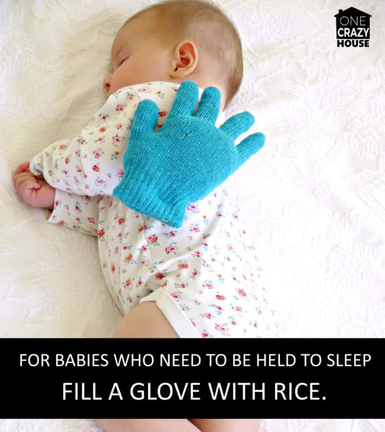 weighted hand on sleeping baby which is a baby hack for babies who need to be held to sleep