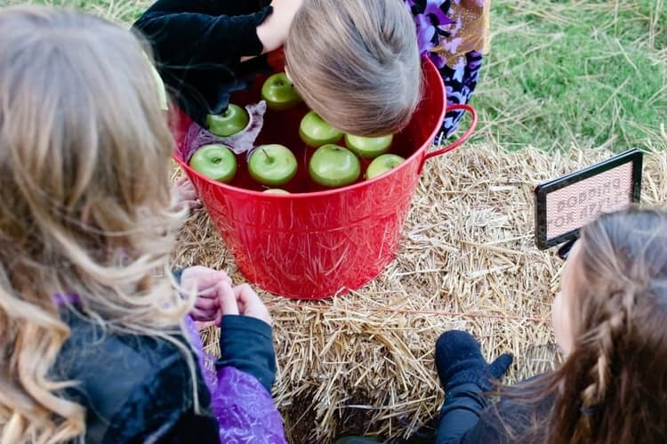 one kid bobbing her head for apples in a bucket filled with water and some apples while 2 other kids are watching
