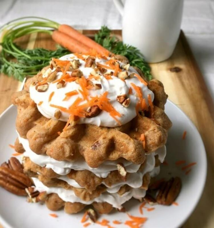 a stack of carrot cake waffles on a plate with cream frosting in between them sitting on top of a cutting board with a beverage mug on the side