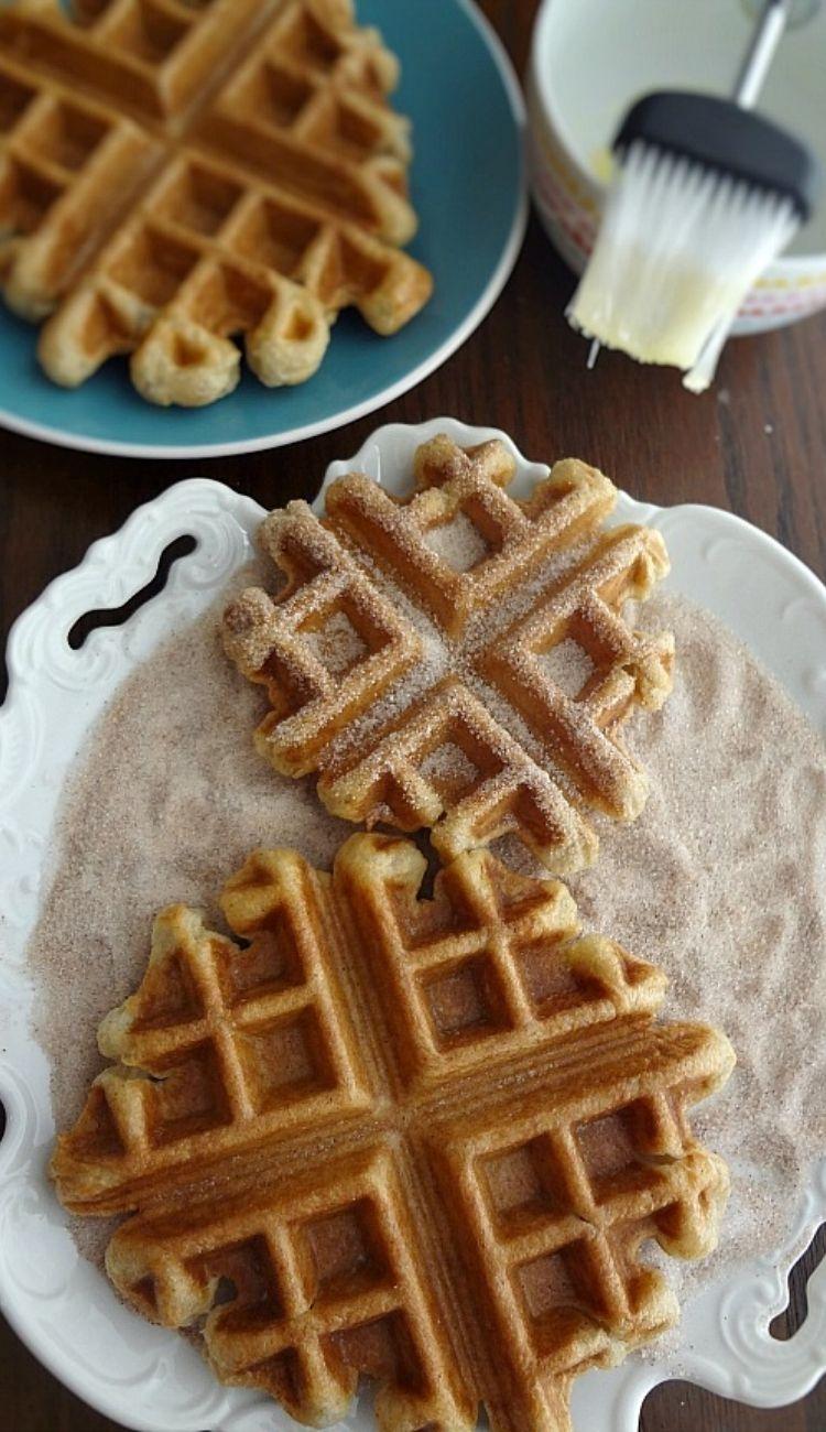 a plate of churro waffles laying on top of cinnamon sugar