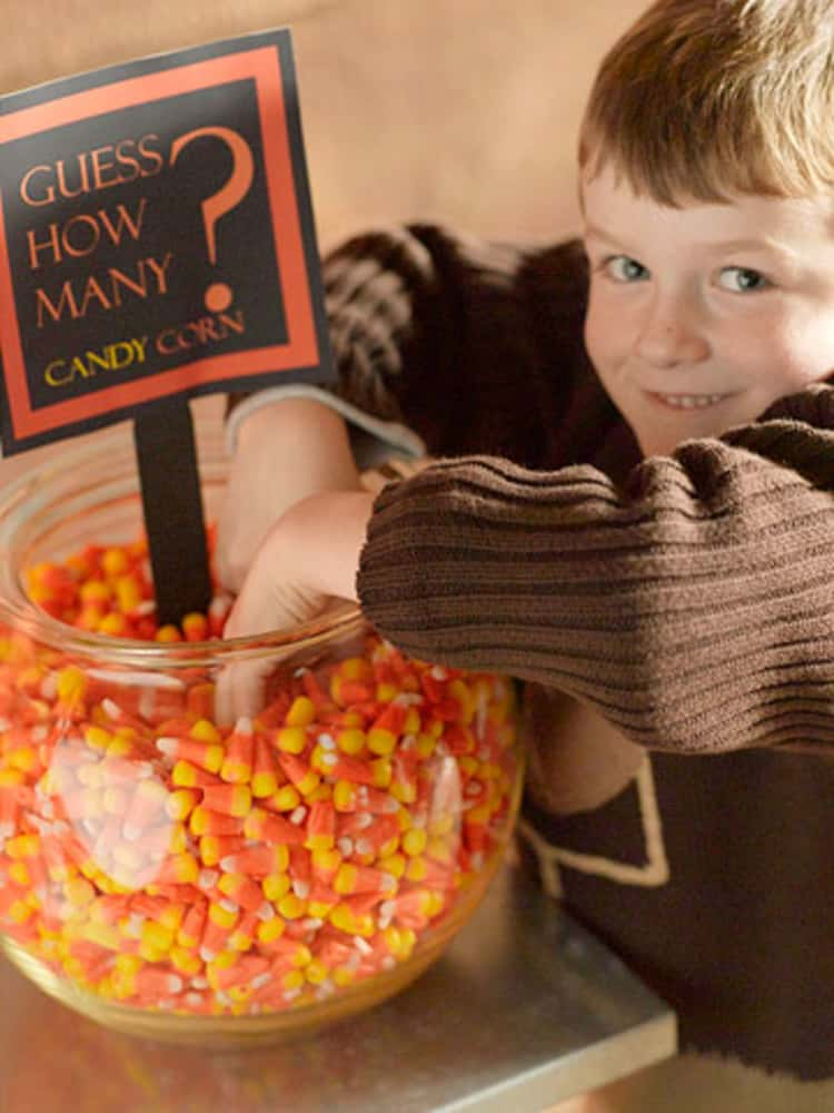"""kind with bowl in fingers inside a bowl of candy corn being used for the """"Guess How Many"""" candy corns there are in the bowl"""