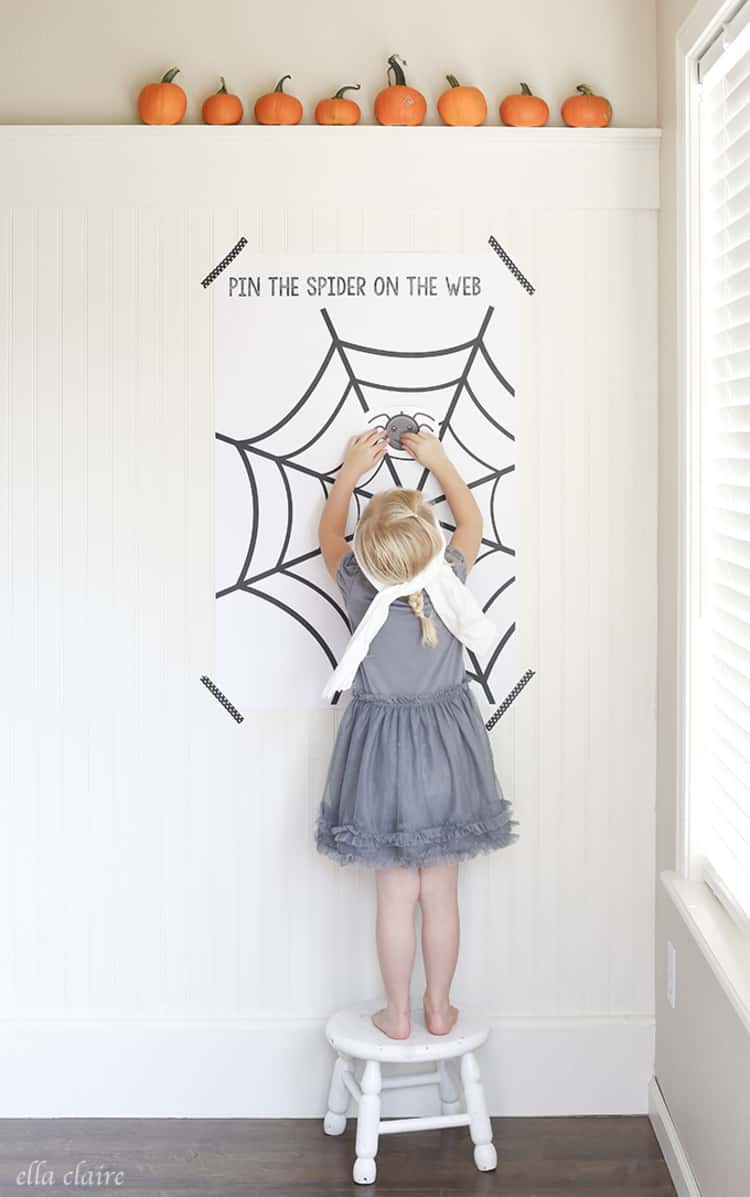 blindfolded kid on a stool playing Pin the Spider on The Web Halloween Game