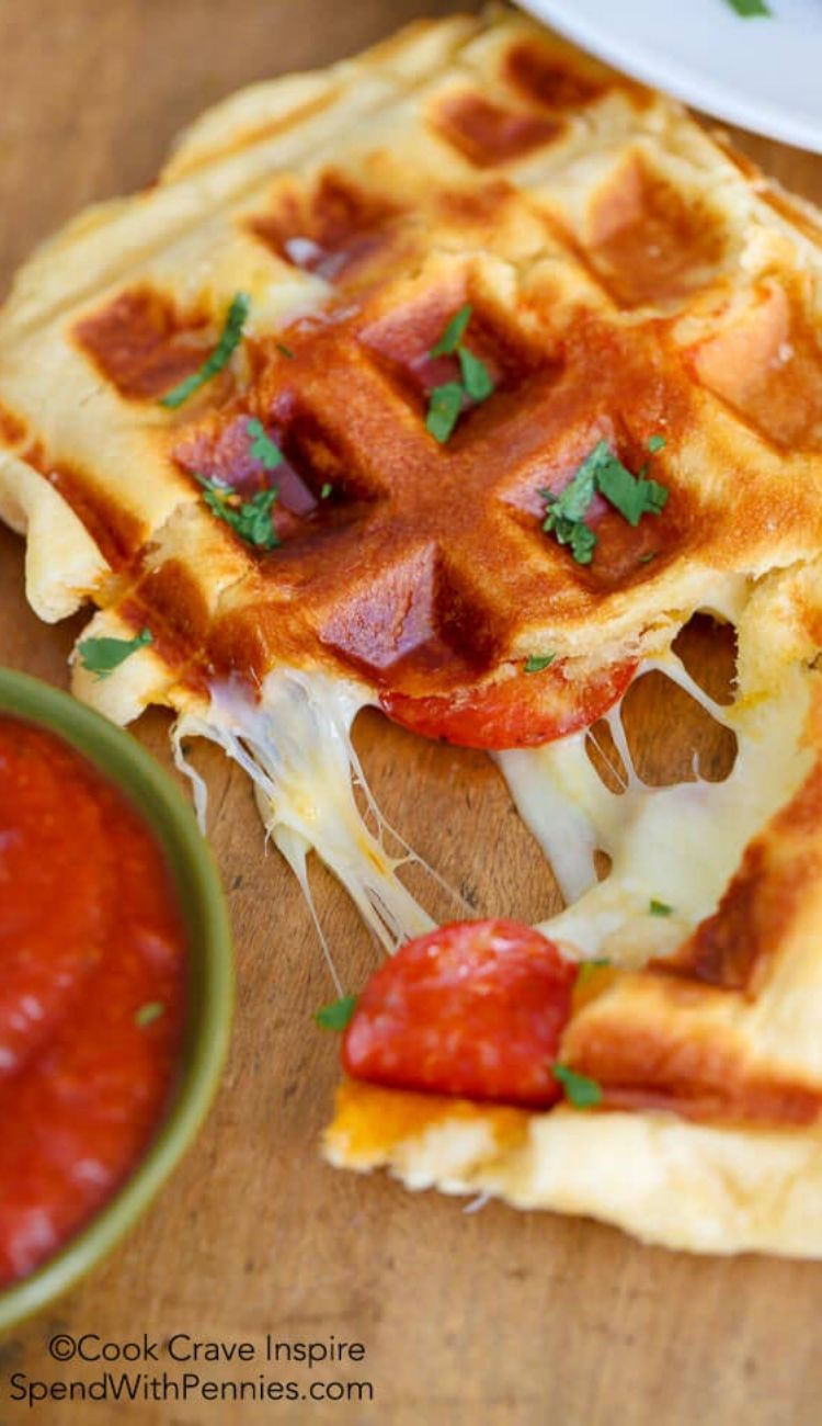 pizza waffles on a cutting board with a side of marinara sauce