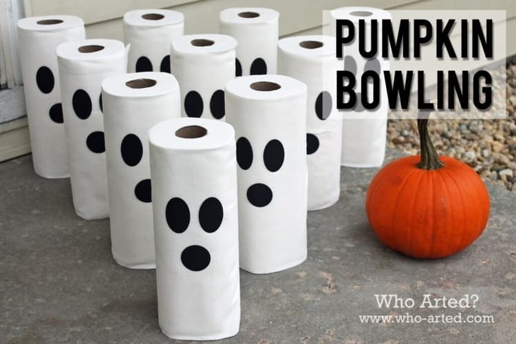 toilet paper rolls with black stickers to make for spooky faces and a pumpkin to be used in the pumpkin bowling halloween game