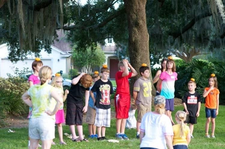 kids balancing mini pumpkins on their heads in readiness for a pumpkin run as part of Halloween games