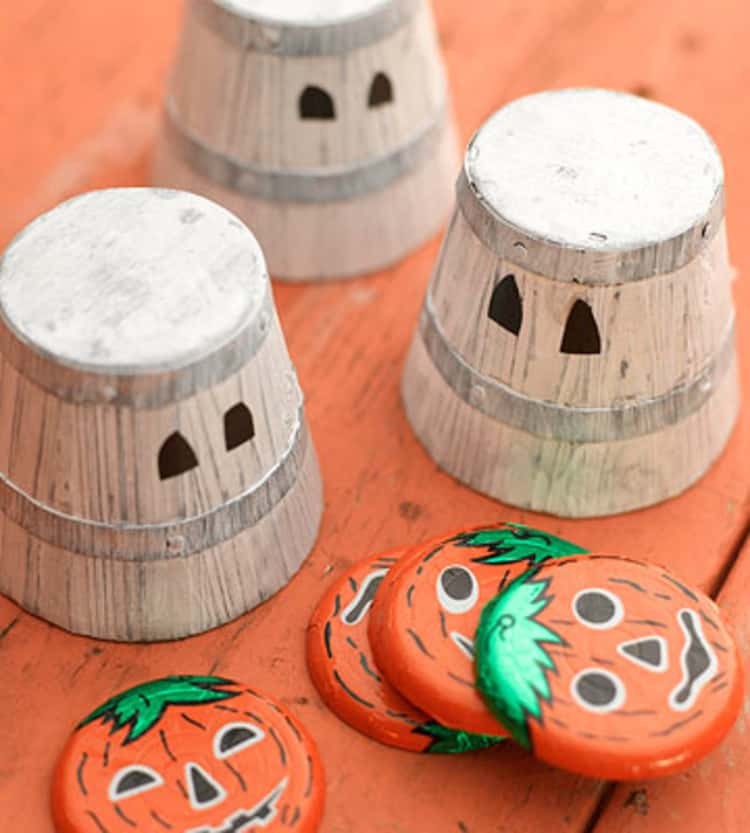 3 upside down spooky pails and plates set up in readiness for the guess which cup/pail Halloween game
