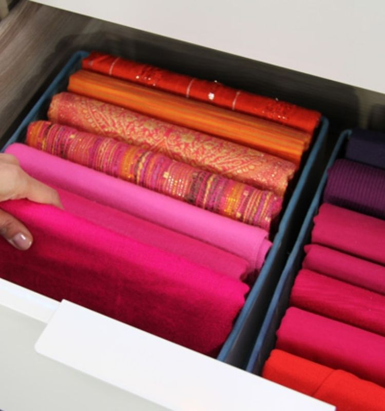 red colored scarves folded and lined upward in an open drawer