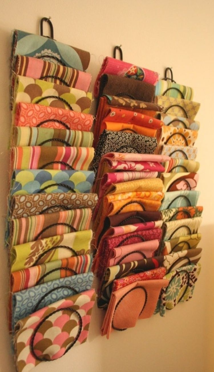 mail sorter attached to a wall with scarves folded in slots