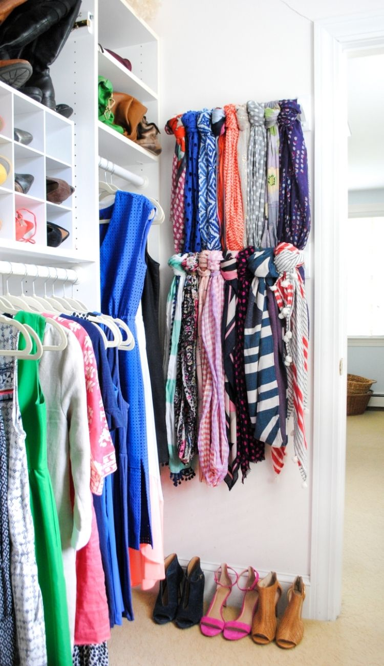 scarves looped around towel bars hanging on a closet wall