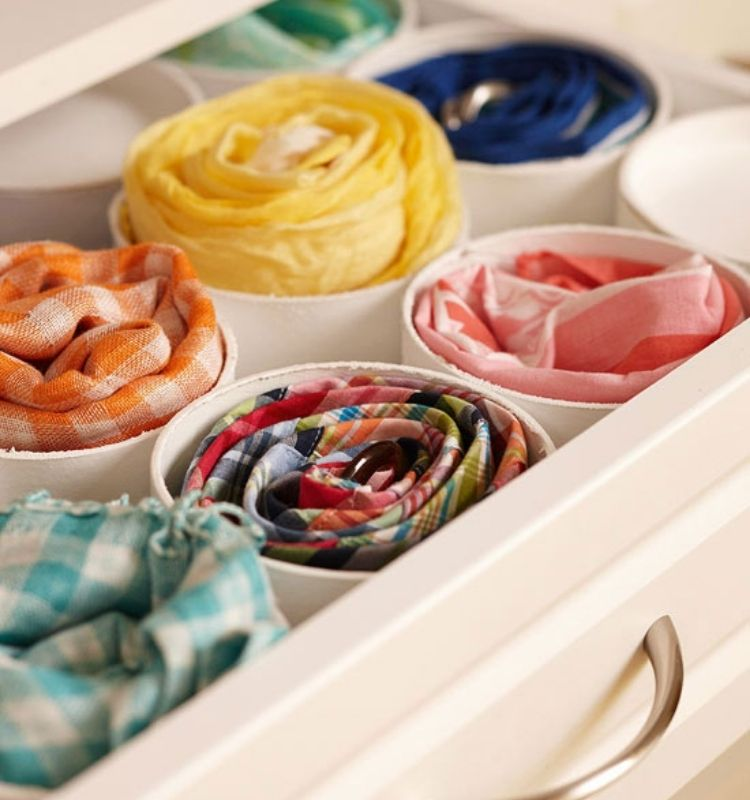 scarves rolled up and stored in a piece of pvc pipe in a drawer