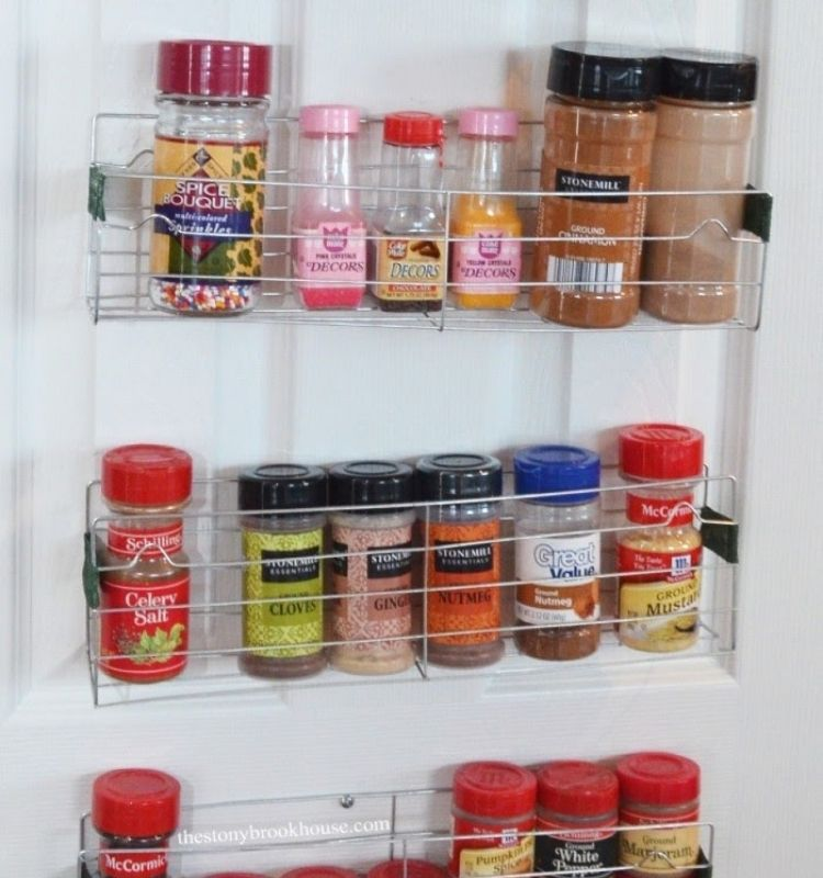 spices in their original jars lined in a DIY rack attached to a door