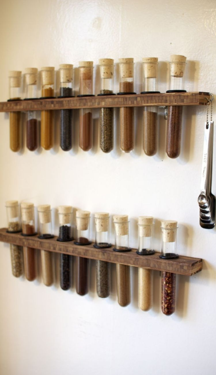 spices in test tubes lined in a wooden holder attached to a wall