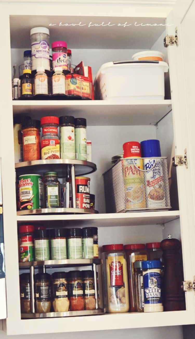 spices on a lazy susan in a kitchen cabinet