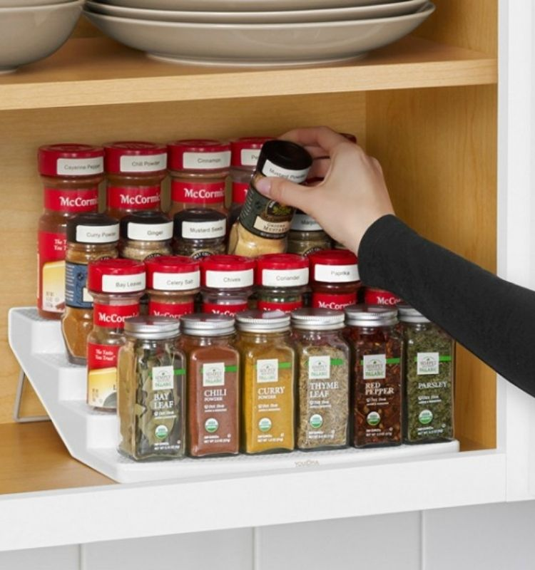 a hand placing a spice jar back on a tiered rack full of other spices