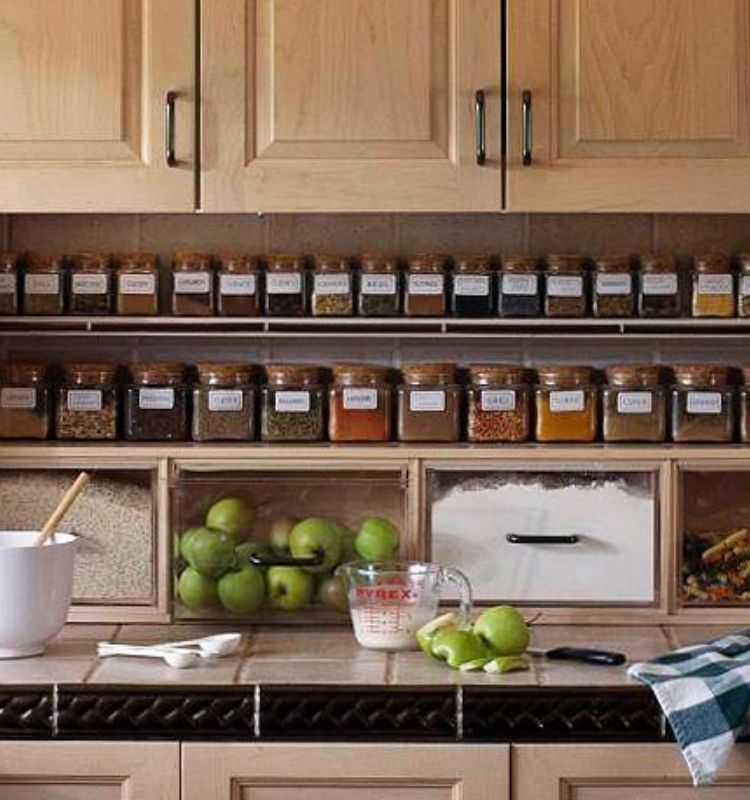 spices in matching jars lined up on a shelf under kitchen cabinets