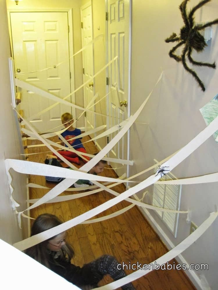 2 kids trying to make their way through a spider lair made from streamers and plastic spiders