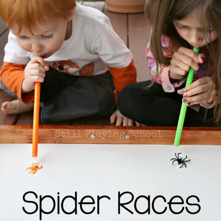 2 kids blowing their spiders in a competitive Halloween Spider Races game