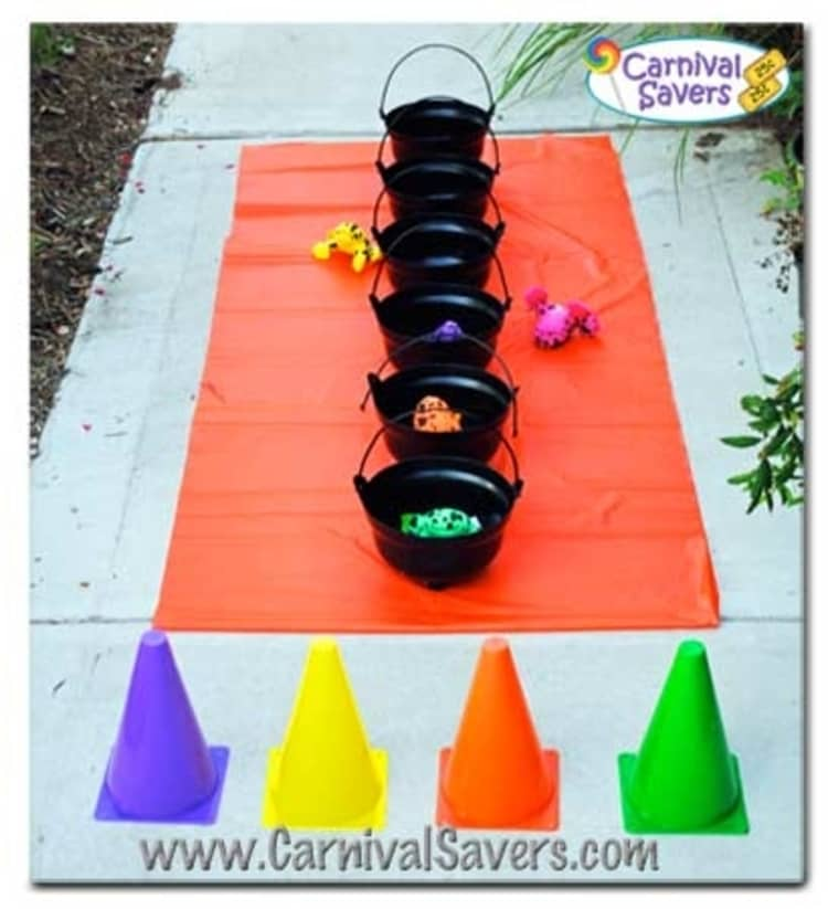 set up for The Witches Brew halloween game where children line up and compete to throw plastic frogs into a row cauldrons