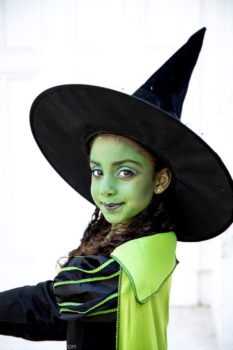 girls dressed as a wicket witch with green face paint