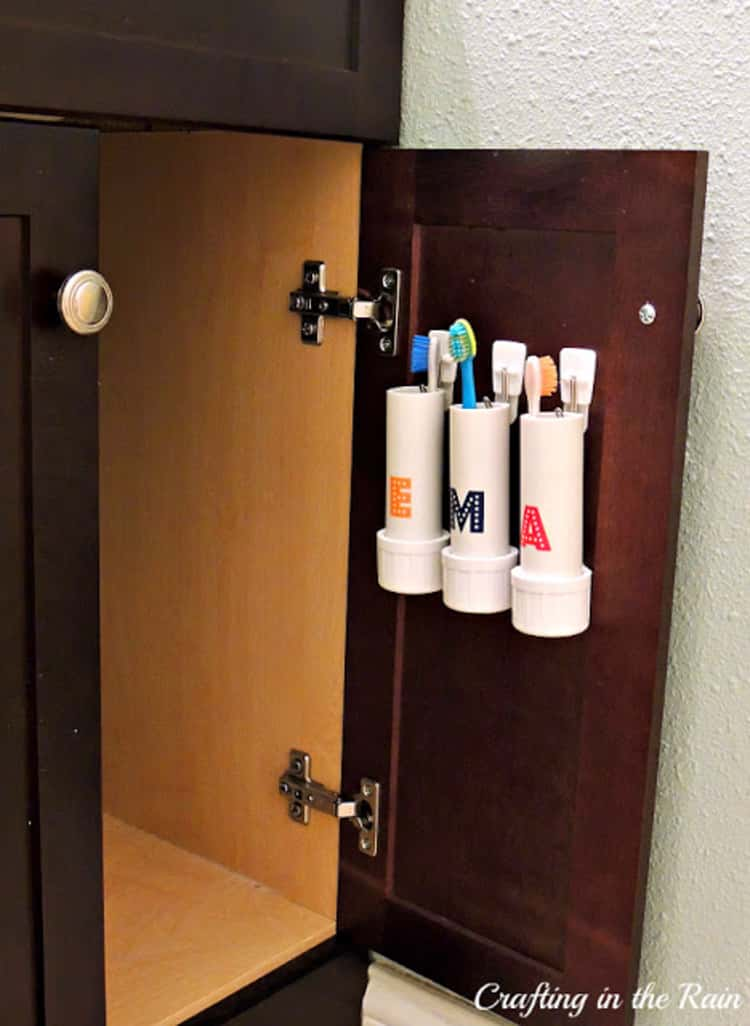 PVC Pipe Toothbrush holders on the inside of a cabinet door