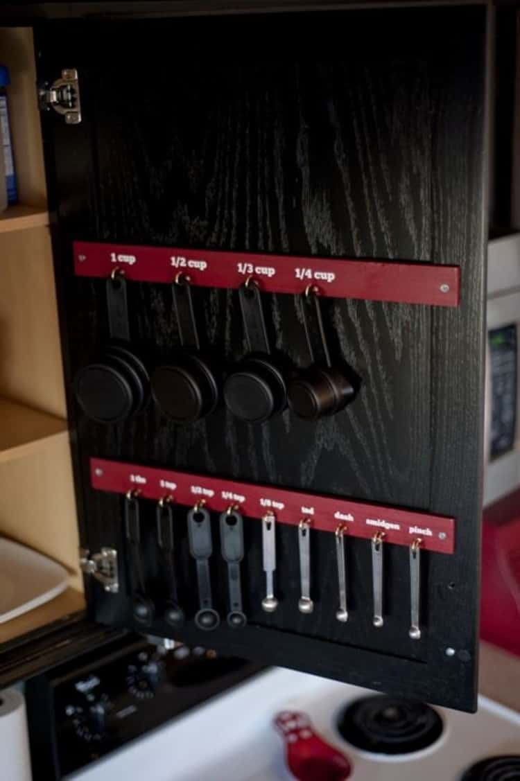 hang measuring spoons and cups on the inside of of a cabinet.